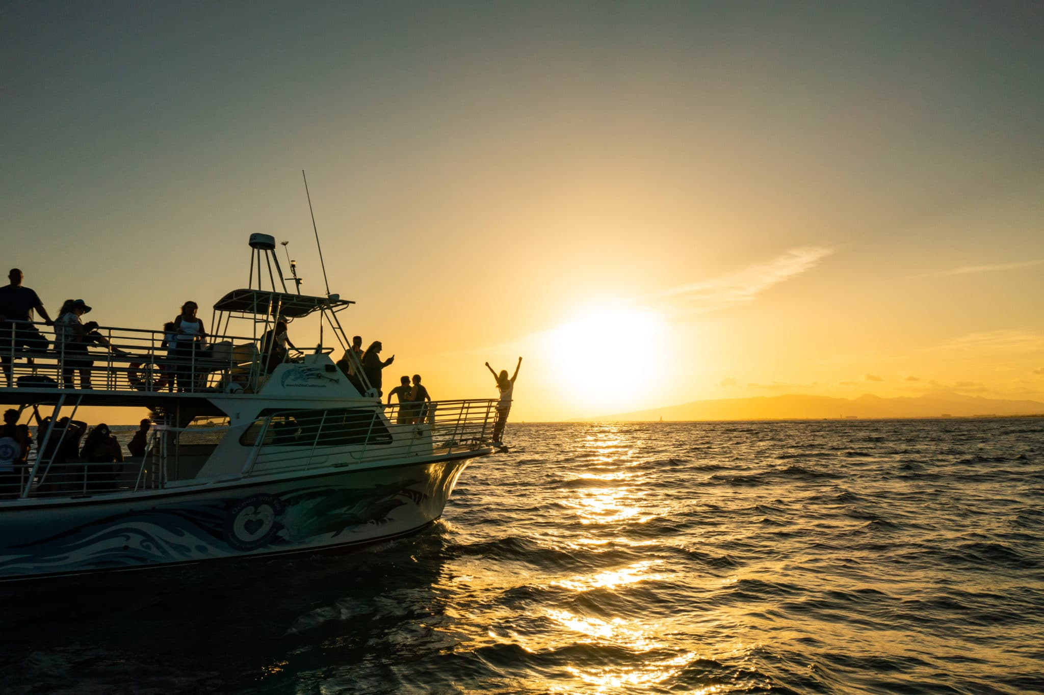 Ocean and You guest enjoys a sunset on Hawaii boat tour